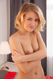 Raena Strips And Poses Nude On A Bed